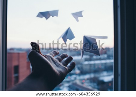 A man's hand lets go little paper planes out of window to nowhere #604356929
