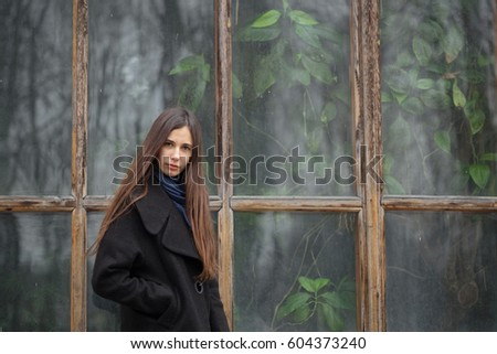 Portrait of a beautiful girl on the background of a large window. #604373240