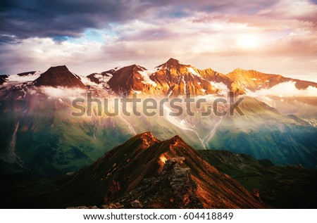 A look at the sunlit hills at twilight. Dramatic evening scene. Location place Grossglockner High Alpine Road, Austria. Europe. Climate change. Drone photography. Explore the world's beauty.