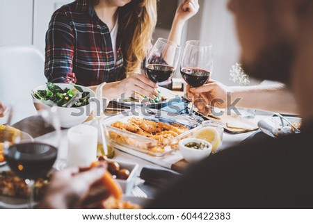 Happy friends cheering with glasses of red wine at restaurant with healthy food, group of people enjoying and toasting at home, togetherness and friendship concept, filtered image #604422383