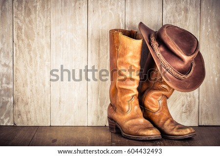 Wild West retro leather cowboy hat and old boots. Vintage style filtered photo #604432493