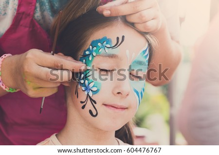 Child face art made to little girl. Blue butterfly painting. Children birthday party entertainment