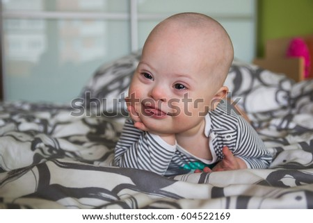 Portrait of cute baby boy with Down syndrome on the bed in home bedroom #604522169