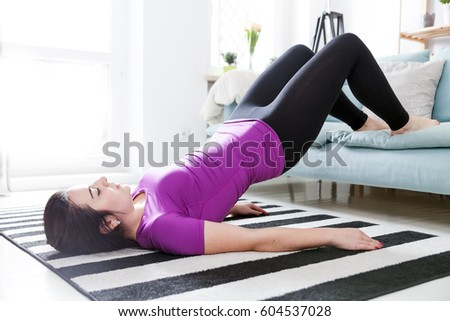 Young woman exercising on carpet at home, interior #604537028