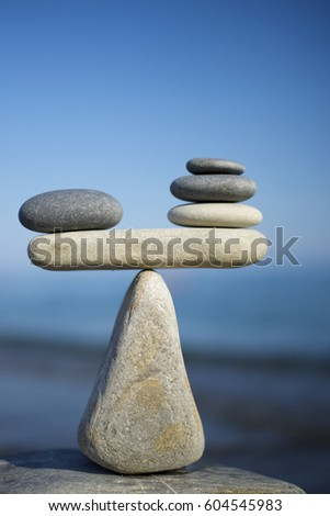 Balance of stones on a blue sky background with a copy space. To weight pros and cons. #604545983