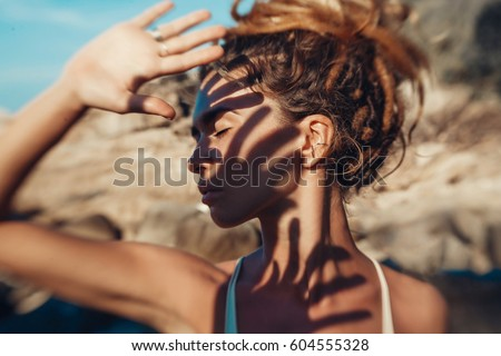 young woman cover her face with hand outdoors. Photo was taken with lens baby #604555328