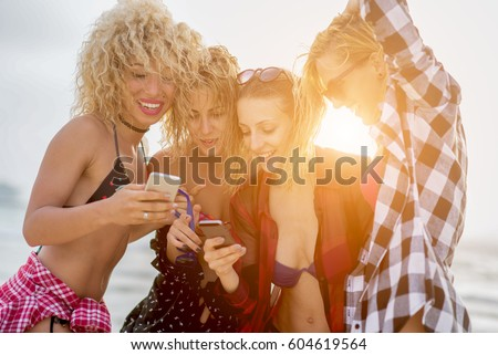 Girlfriends in cool summer look, chilling at beach, having good time. Standing in the sun.