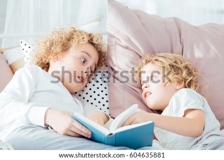 Boy reading book to his younger brother, lying in bed #604635881