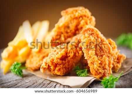 Fried chicken wings on wooden table. Breaded Crispy fried kentucky chicken tasty dinner Royalty-Free Stock Photo #604656989