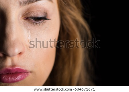 Close-up view of young crying woman's face  isolated on black #604671671