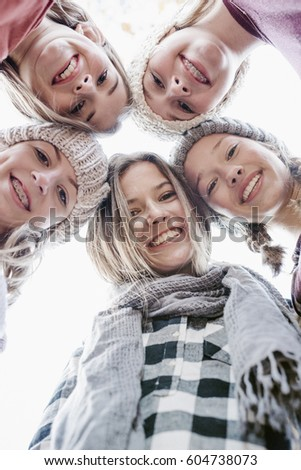 A group of five teenage girls outdoors in woolly hats and scarves #604738073