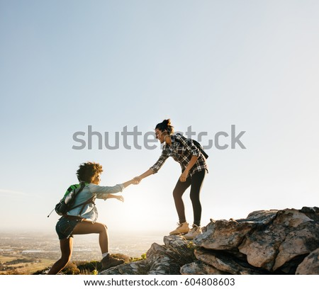 Female friends hiking help each other in mountains. Young female hiker helping friend while trekking in mountain. Royalty-Free Stock Photo #604808603