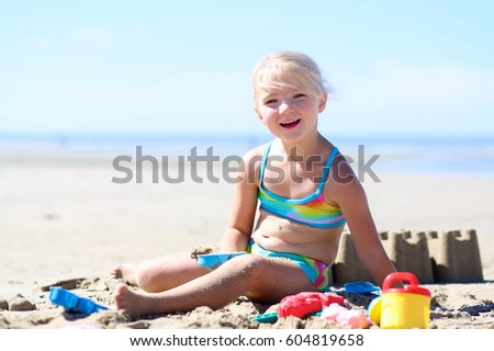 Happy little girl playing with toys on the beach. Cute toddler building sand castles on a sunny day. Family enjoying sea vacation.  #604819658