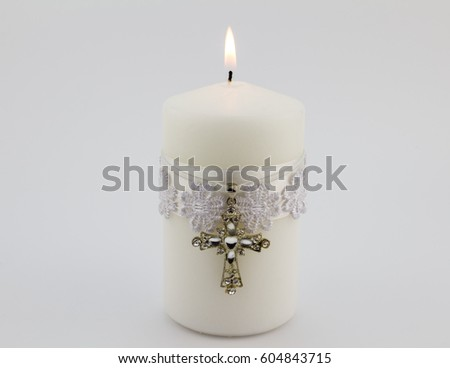 White candle with lace, ribbon and Christian cross pendant isolated on white background