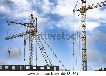 Construction cranes against a blue sky with clouds #604854608