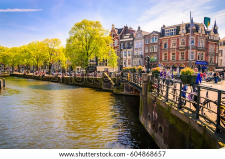 AMSTERDAM, NETHERLANDS - MAY 5, 2016: Traditional old buildings and and boats in Amsterdam, Netherlands #604868657