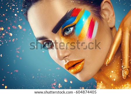 Fashion Model Girl with colored face painted. Beauty fashion art portrait of beautiful woman with colorful abstract makeup. Vivid paint make-up, bright colors. Vogue style lady , Multicolor design.