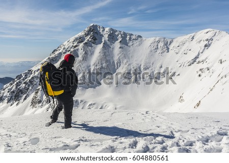 Hiker with backpack and ice ax during a winter trip in the mountains admiring the peaks. #604880561