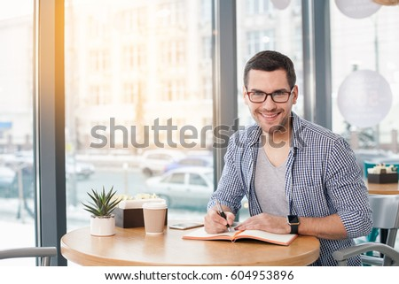Coffee time. Handsome young man in cafe with big window. Man with cup of coffee to go. Man with glasses looking at camera and smiling #604953896