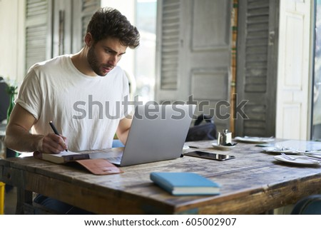 Beautiful bearded international student writing notes in notebook and searching new information creative ideas for future studying project using laptop with wireless connection and modern laptop #605002907