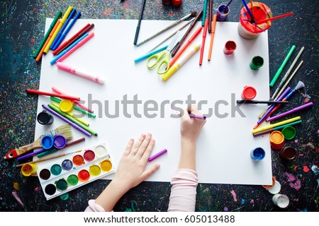 Hands of a kid drawing with highlighters on paper Royalty-Free Stock Photo #605013488