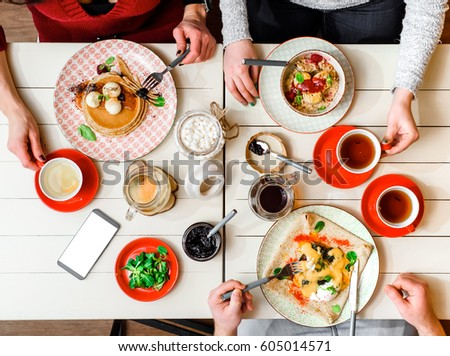 breakfast Pancakes with friends. Top view of group of people having dinner together while sitting at the white wooden table #605014571