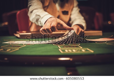Croupier behind gambling table in a casino. #605080553