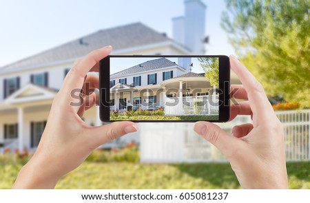 Female Hands Holding Smart Phone Displaying Photo of House Behind. #605081237