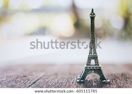 Small model Paris Eiffel Tower on wooden table with blurred background (Vintage filter effect). #605115785