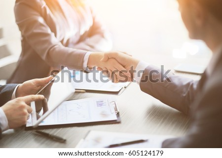 Business people shaking hands, finishing up meeting #605124179