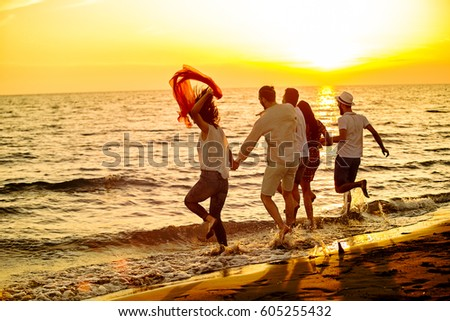 Group of happy young people is running on background of sunset beach and sea #605255432