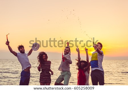 Young People Dancing On Beach at Sunset #605258009