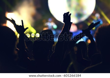 Crowd rocking during a concert with raised arms. Toned image #605266184