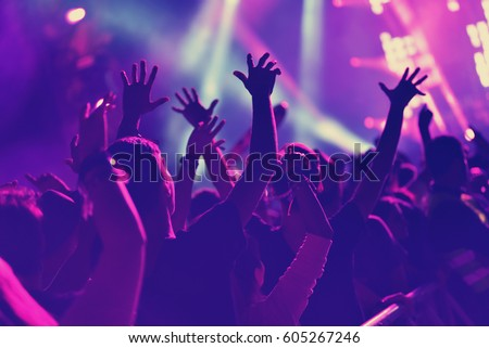 Rear view of crowd with arms outstretched at concert Royalty-Free Stock Photo #605267246
