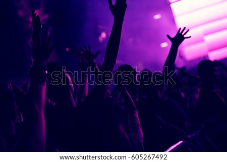 Crowd rocking during a concert with raised arms. Toned image #605267492