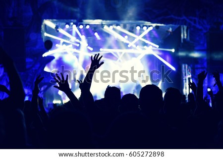 Crowd rocking during a concert with raised arms. Toned image #605272898