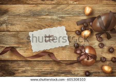 """Easter background with golden and chocolate egg, candy, silk ribbon on a wooden table, a note with the words """"Happy Easter""""  #605308103"""