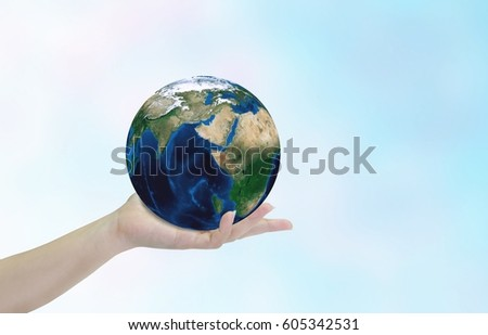 Close up women's hand holding planet Earth on blue sky. Earth's day concept.Elements of this image furnished by NASA. #605342531