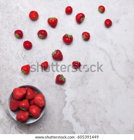 Flatlays. Top view of fresh strawberries scattered and in a plate on a marble surface #605391449