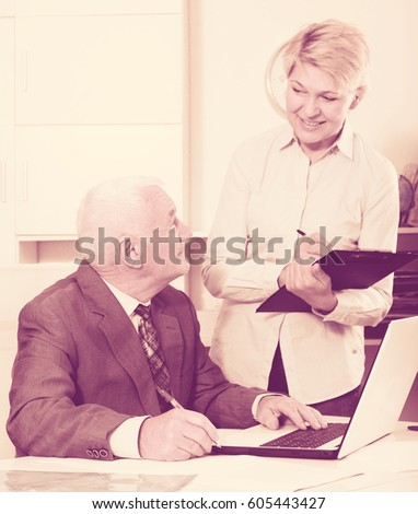 Senior manager and secretary working effectively together in office #605443427