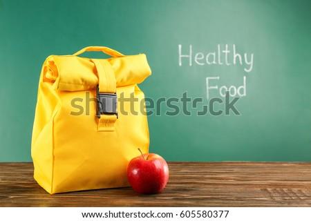 Lunch bag on wooden tabletop against chalkboard background #605580377