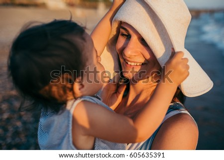 Lifestyle of young mother playing with daughter with white hat at the sea and beach background. Family vacation. Travel. Cute female play with cheerful toddler. Caucasian female with baby at ocean. #605635391