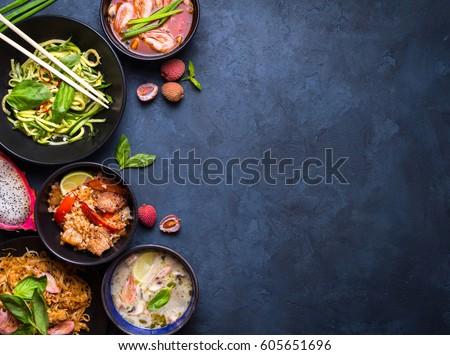 Thai food background. Dishes of thai cuisine. Tom yum, tom kha gai, pad thai noodles, fried rice with pork and vegetables khao phat mu, green papaya salad som tam, thai fruits. Space for text #605651696