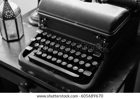 old weathered black and white typewriter sitting on dusty black desk good for any author, writer, journalist or editor. wooden desk provides a vintage design and feel for the aspiring artist.  #605689670