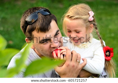 Portrait of father and daughter eating apples together outside. #605721257