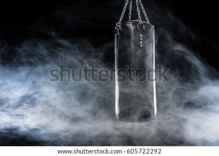 Black punching bag in empty room filled with smoke  isolated on black Royalty-Free Stock Photo #605722292