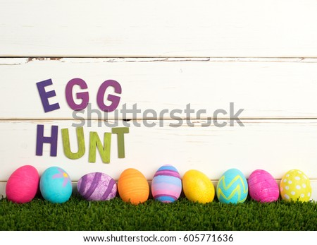 Easter Egg Hunt Invitation with Colorful Dyed Eggs in a line on grass and against White Shiplap Board Background with room or space for your words, copy, text or letters.  It's a horizontal side view #605771636