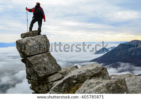 climber on the rocks watching the foggy landscape #605785871