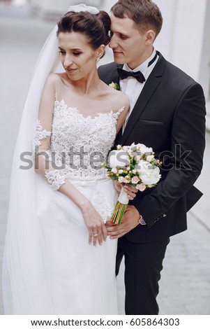 bride and groom standing on the street near the high white wall with a bouquet of flowers #605864303
