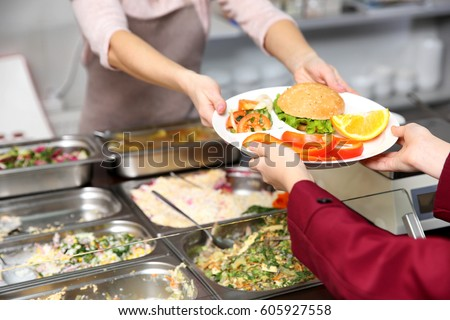 Pleasant woman giving lunch to school girl in cafeteria Royalty-Free Stock Photo #605927558